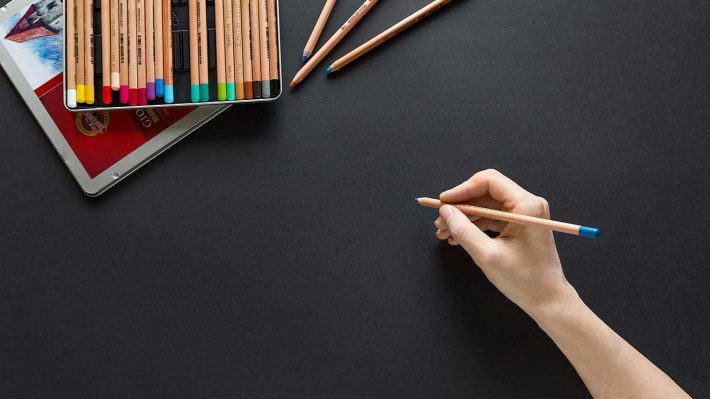 Black surface, hand with colored pencil waiting to draw or write something