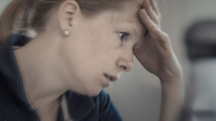 Woman clutching forehead in front of computer, stressed out look on her face