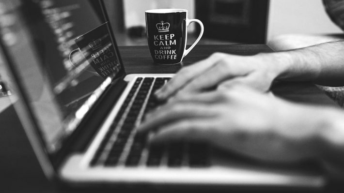 "hands on computer keyboard, cup with text ""Keep calm - drink coffee"" in background"