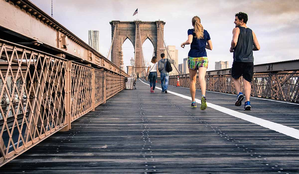 Woman and man running on the Brooklyn bridge