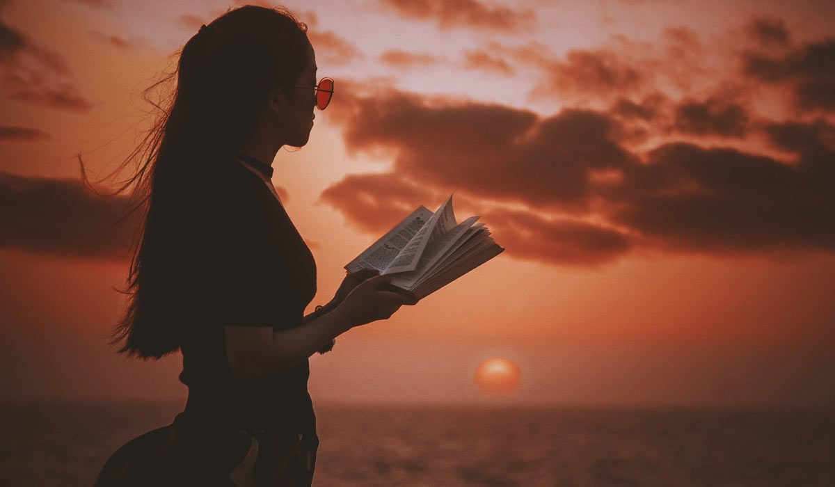 woman standing with open book, looking at sea and horizon with sunset