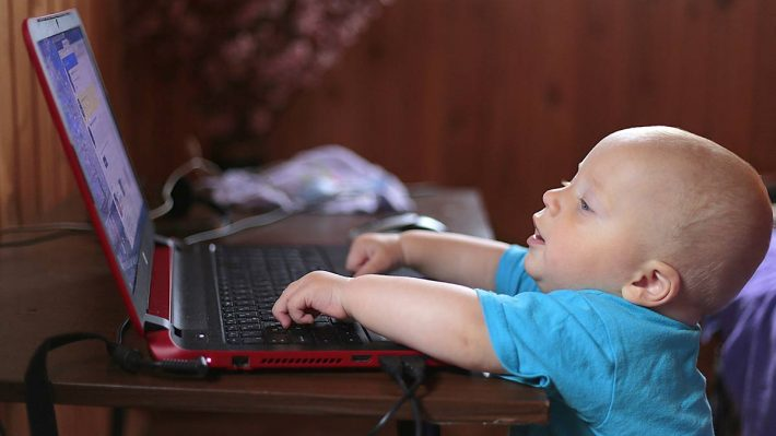 small child in front of computer, with hands on keyboard
