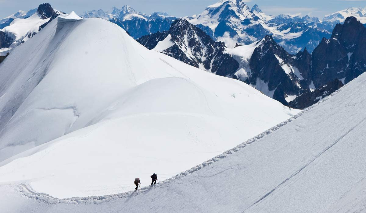 Mountain climbers going up on snowy mountains with mountain range in background