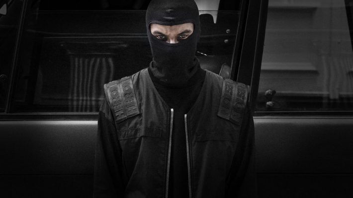 Masked man dressed in black standing by black SUV