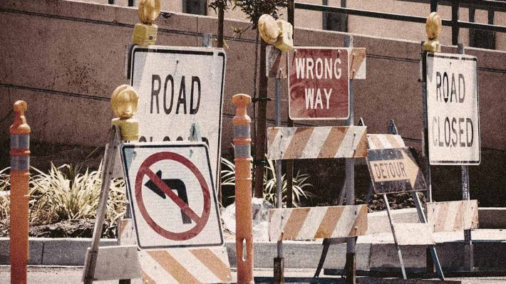 """A group of """"road closed"""" signs blocking the road"""