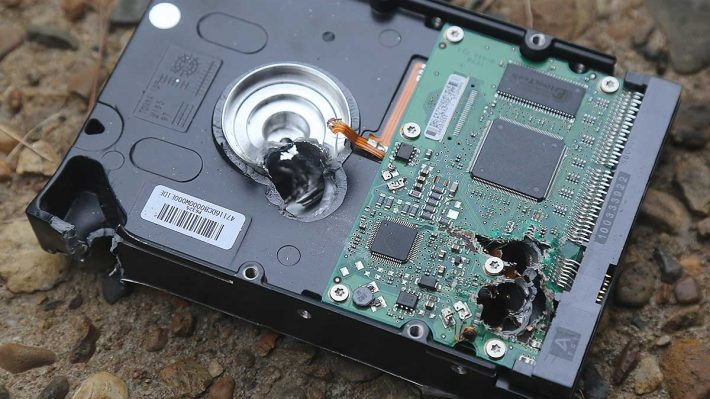 Hard drive that has been shot through with multiple bullets