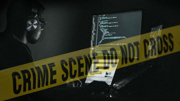 """Crime scene do not cross"" tape across image of man in dark room working on computer with multiple monitors"