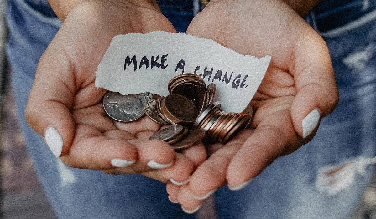 "hands holding a bunch of coins and paper with words ""Make a change"""