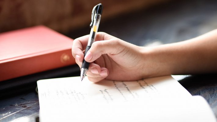 Closeup of woman's hand holding a pen over a journal as she is journaling