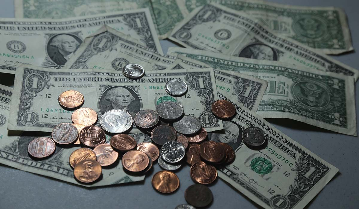 $1 bills and coins spread on table top