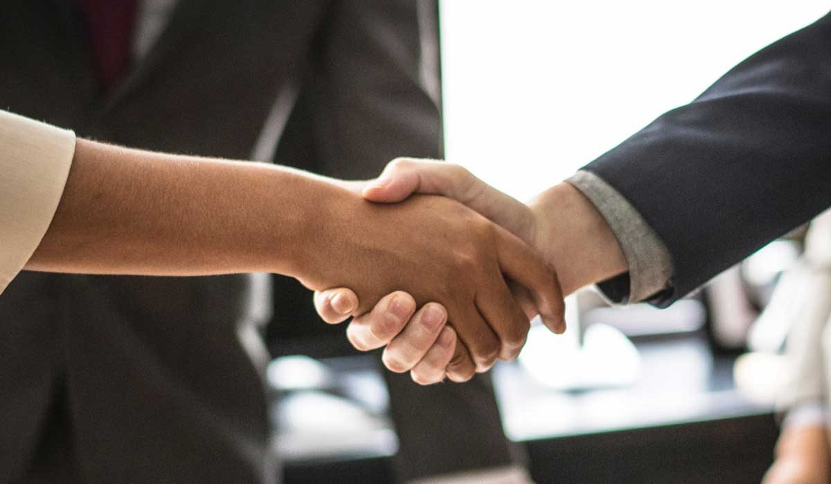 African-American woman and caucasian man shaking hands