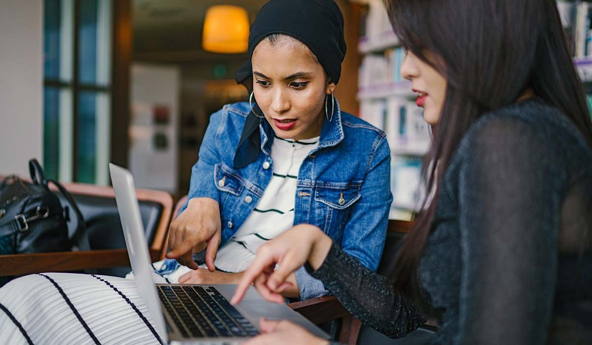 Women looking at computer together, talking
