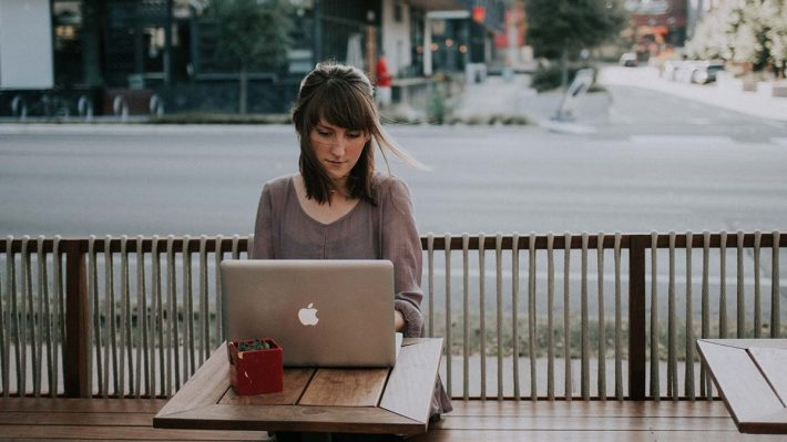 woman with computer outside at table