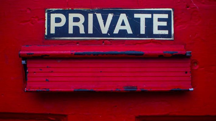 "Sign ""private"" over a mail drop on a door"