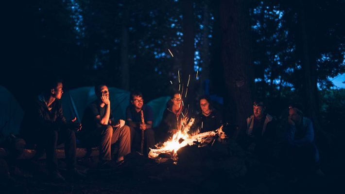 Men and women sharing stories around a campfire