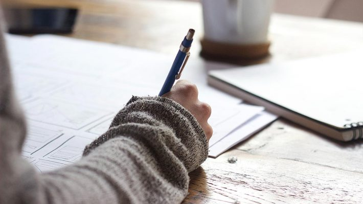 Closeup of hand holding pen, desk, paper
