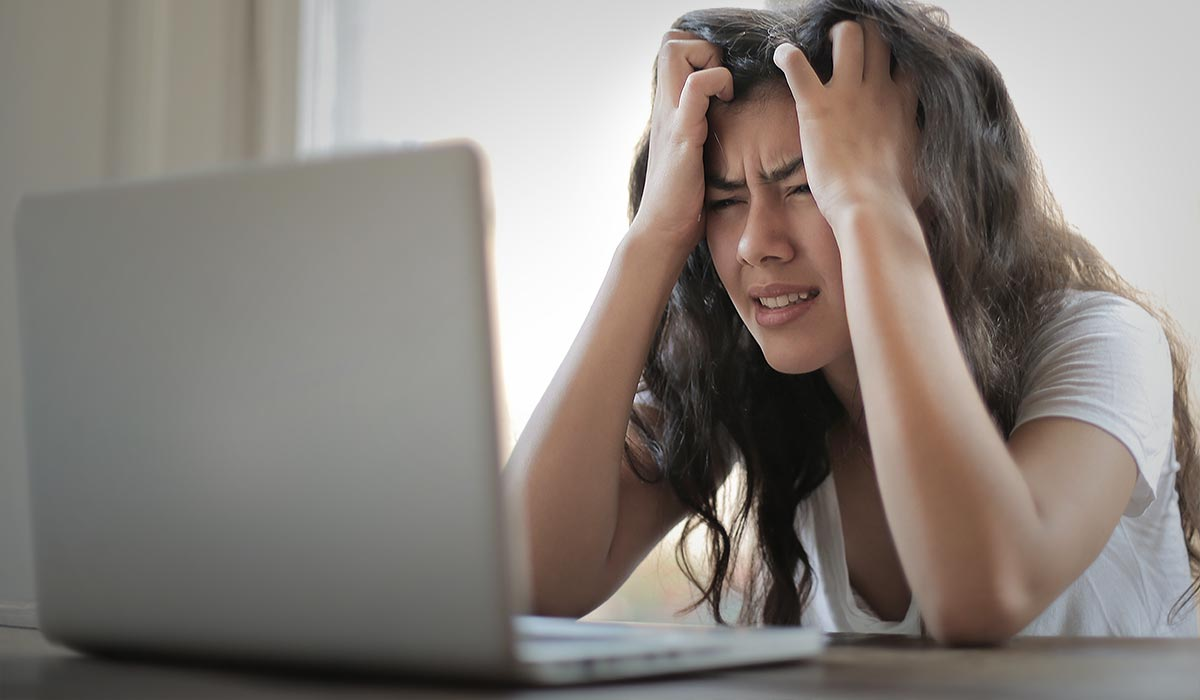 Frustrated woman in front of computer, tearing her hair