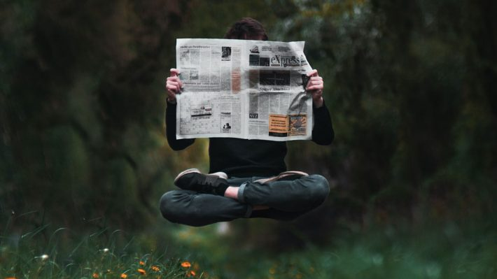 levitating man reading newspaper