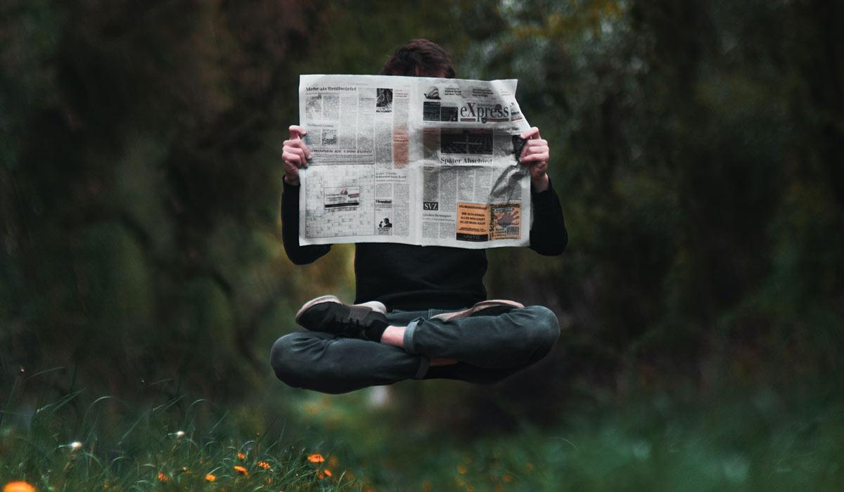 levitating man reading newspaper